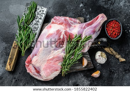 Raw lamb shoulder meat ready for baking with garlic, rosemary. Black background. Top view Royalty-Free Stock Photo #1855822402
