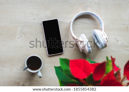 Top view of a wooden table with a poinsettia, wireless headphones, mobile phone and a cup with coffee