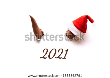 Two brown bull horns break through the white background.On one horn is a Santa Claus hat.Bull as a symbol of the New year 2021.The inscription of a 2021.Creative New Year and Christmas concept. Royalty-Free Stock Photo #1855862761