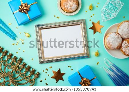 Jewish holiday Hanukkah concept with photo frame mock up, menorah, sufganiyah and gift box over blue background