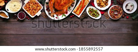 Classic Christmas turkey dinner. Overhead view top border on a dark wood banner background with copy space. Turkey, potatoes and sides, dressing, fruit cake and plum pudding.