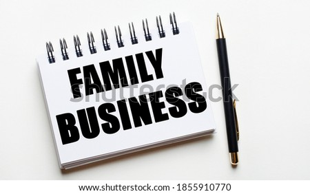 On a light background, a white notebook with the words FAMILY BUSINESS and a pen.