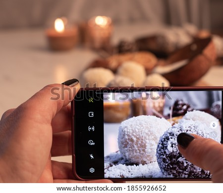 Hands taking picture with mobile phone of homemade brownies with coconut flour and white chocolate cookies on wooden board, burning candles on white wooden table. Soft focus background