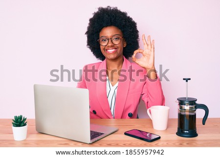 Young african american woman working at desk using computer laptop doing ok sign with fingers, smiling friendly gesturing excellent symbol