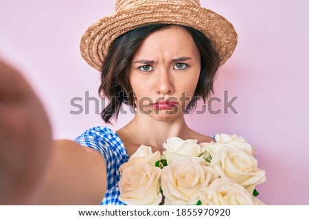 Young beautiful girl wearing summer hat taking a selfie depressed and worry for distress, crying angry and afraid. sad expression.