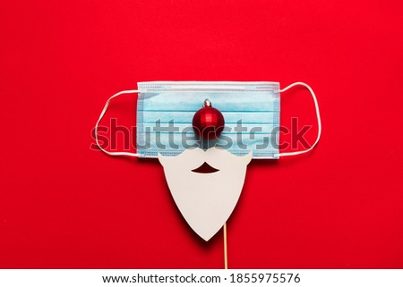 Festive christmas Santa Claus face made from face mask and decorations Royalty-Free Stock Photo #1855975576