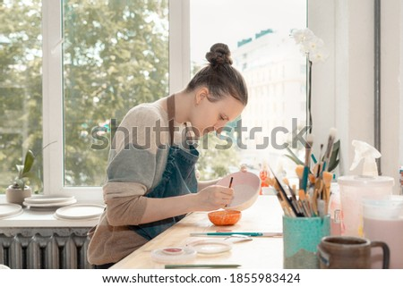 Skilled young woman in apron sitting at table and drawing on ceramic bowl in pottery workshop. Earn extra money, side hustle, turning hobbies into job. Royalty-Free Stock Photo #1855983424