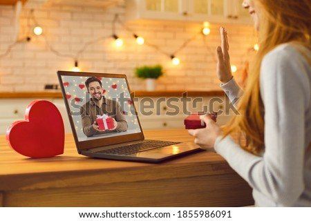 Long-distance relationship and virtual date in lockdown. Young couple in love video calling each other during quarantine and showing gifts and presents they prepared for Saint Valentine's Day Royalty-Free Stock Photo #1855986091