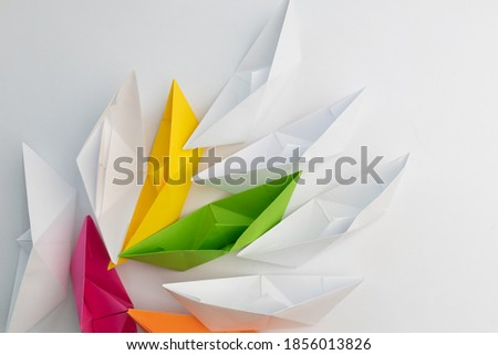 White and Colorful Origami Boats on Light Background