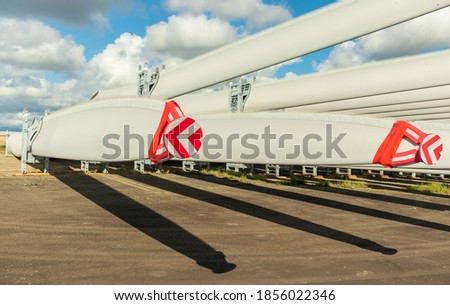 Rack of new large wind turbine blades with caps on the tips. Royalty-Free Stock Photo #1856022346