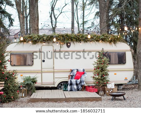 Vintage old travel trailer with Christmas decorations, Christmas tree, chair and Christmas lights. Cozy home, camping before Christmas holidays. #1856032711
