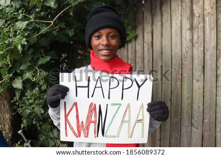 Kid in winter clothing holding Happy Kwanzaa sign outdoors