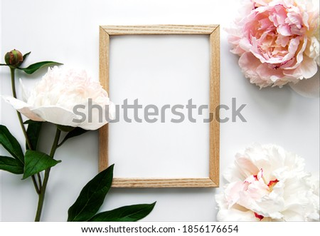 Wooden frame surrounded by beautiful pink peonies on a white background, top view, copy space, flat lay. Mockup greeting card, invitations to a holiday or wedding. Bright summer flower concept. Royalty-Free Stock Photo #1856176654