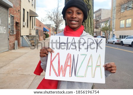 Black kid holding Happy Kwanzaa sign outdoors on city street