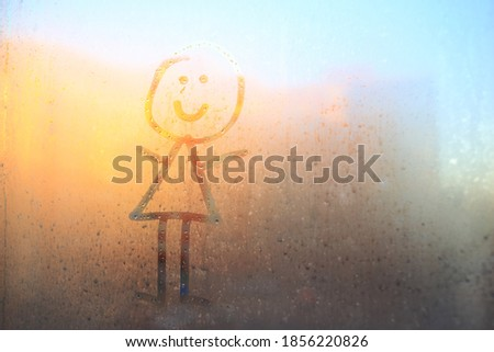 Children's drawing on the window. A man drawn on a fogged window.The silhouette of a man on the fogged glass. Girl on the background of the window