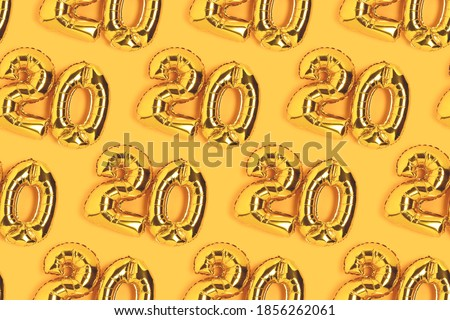 Numbers 20 golden balloons pattern. Twenty years anniversary celebration layout on a yellow background. Royalty-Free Stock Photo #1856262061