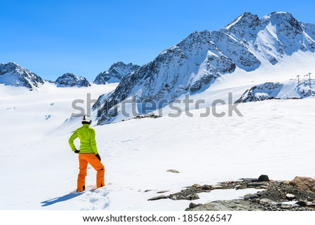 Young woman alpine skier in orange pants and green jacket stands in fresh snow on Pitztal Glacier in Austrian Alps #185626547