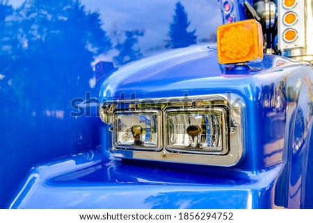 Front part of commercial freight transportation stylish blue big rig semi truck tractor with chrome accessories and trim on glass headlight and reflecting shiny painted surface