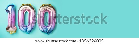 Rainbow foil balloon number, digit one hundred. Birthday greeting card with inscription 100. Anniversary concept. Top view. Colored numeral on blue background. Numerical digit, Celebration event. Royalty-Free Stock Photo #1856326009