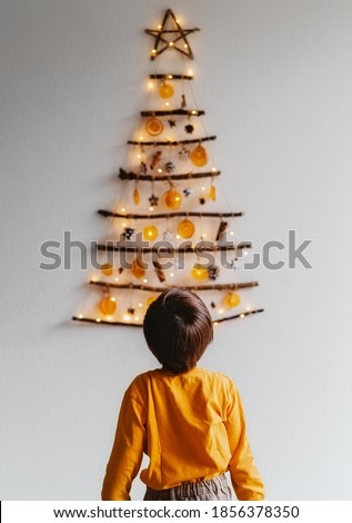 Back view of child looking at handmade craft Christmas tree made from sticks and natural materials hanging on wall. Sustainable Christmas, zero waste, plastic free, eco friendly. Royalty-Free Stock Photo #1856378350