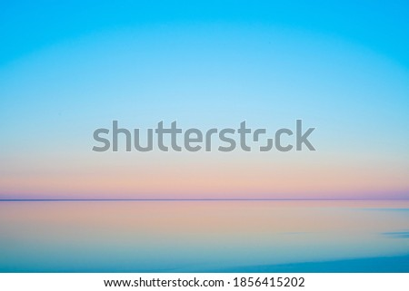 Calm sea water against cloudless sundown sky in summer evening in countryside Royalty-Free Stock Photo #1856415202