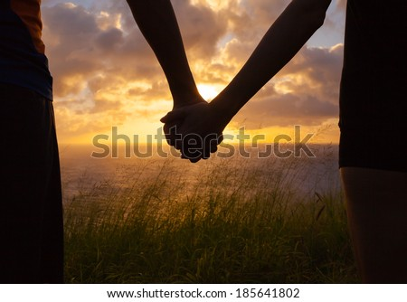Couple holding hands a watching a beautiful sunset in Hawaii. Royalty-Free Stock Photo #185641802