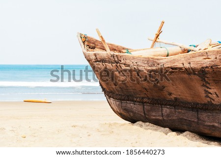 Vintage handmade fisherman boat with fishing nets on the beach near the ocean in Arambol, Goa, India. Sandy coastal of the Arabian Sea, concept travel, tropical resort, vacation in paradise places Royalty-Free Stock Photo #1856440273