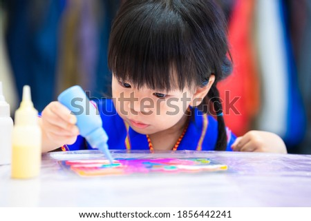 Little girl make art. Child holding a blue water bottle drop paint on a rainbow cartoon character on the table. Kid wearing a blue shirt is 3 years old.