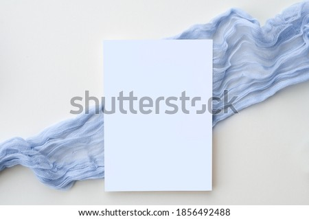 This simple and elegant hand styled photograph features a 5x7 vertical card set on top of a dusty blue gauzy table runner. Perfect for featuring wedding invitations, baby shower invitations, save the  Royalty-Free Stock Photo #1856492488