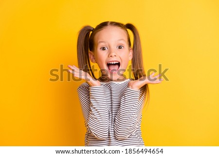 Portrait of young excited shocked crazy smiling girl child kid hold hands isolated on yellow color background Royalty-Free Stock Photo #1856494654