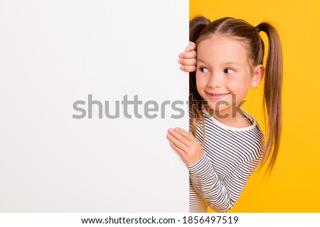 Portrait of young happy smiling curious little girl child kid behind white wall banner look in copyspace isolated on yellow color background Royalty-Free Stock Photo #1856497519