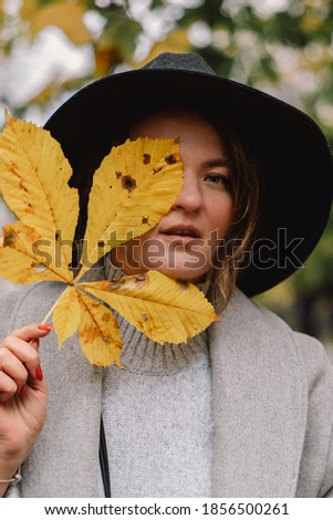 Woman enjoying fall nature. Autumn leaves in girl hands. Autumn mood. Fall time