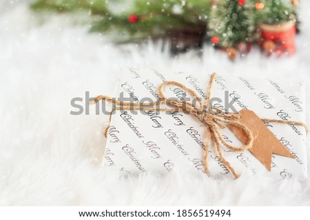 Wrapped Christmas present. Gift has been tied with a brown twine with a paper tag. Selective focus with blurred background and falling snow. Copy space available.