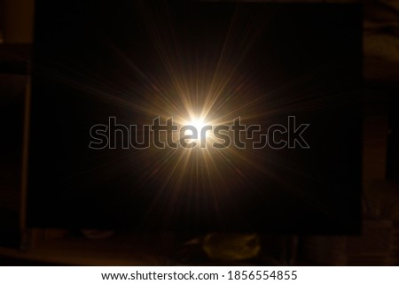 Easy to add lens flare effects for overlay designs or screen blending mode to make high-quality images. Abstract sun burst, digital flare, iridescent glare over black background. Royalty-Free Stock Photo #1856554855
