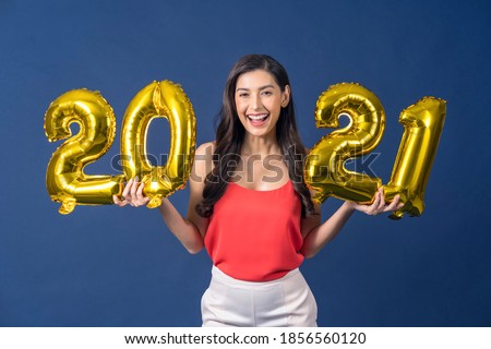 Happy young Asian woman holding 2021 gold color balloons for celebrate merry Christmas and happy new year on blue color background, celebration and decoration for holiday event concept