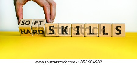 Hard skills versus soft skills. Hand flips cubes and changes the expression 'hard skills' to 'soft skills' or vice versa. Beautiful yellow table, white background. Business concept. Copy space. Royalty-Free Stock Photo #1856604982