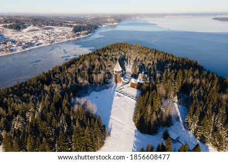 Aerial view of Khokhlovka, wooden ancient houses in winter, Perm and forest with snow in cold sunny day, two rivers connecting together Royalty-Free Stock Photo #1856608477