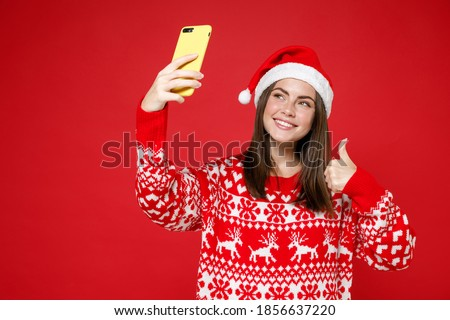 Smiling cheerful young Santa woman in sweater, Christmas hat doing selfie shot on mobile phone showing thumb up isolated on red background studio. Happy New Year celebration merry holiday concept