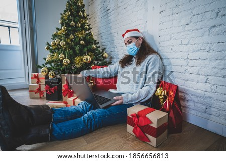 Sad woman with face mask video calling family and friends feeling depressed home alone in lockdown at christmas. COVID-19 virtual holiday celebrations, social distancing, lockdown and mental health. Royalty-Free Stock Photo #1856656813