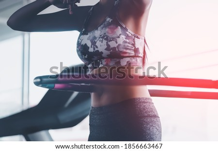 Sporty woman is exercising with Hula hoop in fitness gym for healthy lifestyle concept. Royalty-Free Stock Photo #1856663467