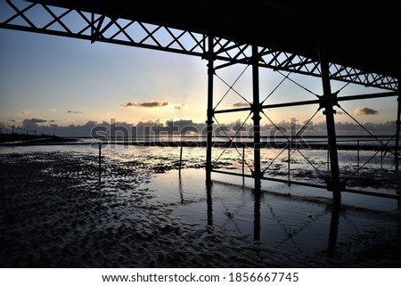 Sunset over expansive beach with metal pier support structure in foreground #1856667745