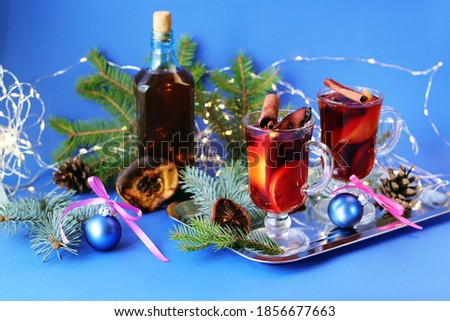 Christmas toys, cups with mulled wine, spices, fir branches and illumination on a blue background, the concept of congratulations, home comfort, postcard #1856677663