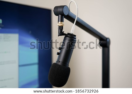 Microphone on a boom arm in front of a screen