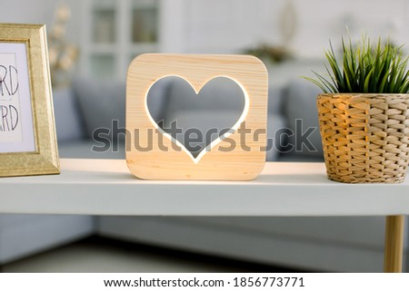 Home interior in living room. Close up image of decorative stylish wooden night lamp with heart picture, on table with flower pot and photo frame.