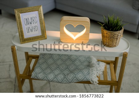 Top angle view of hand made home decor, coffee table with photo frame, decorative wooden lamp with heart picture, and green plant in wicker flower pot. Interior of living room