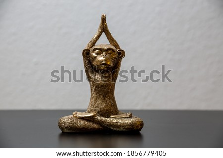 A gold colored meditating monkey statue sitting on a black surface, the background of the picture is white and blurry.