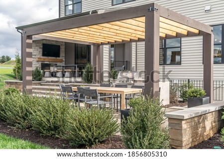 Trendy outdoor patio pergola shade structure, awning and patio roof, dining table, chairs, metal grill surrounded by landscaping Royalty-Free Stock Photo #1856805310