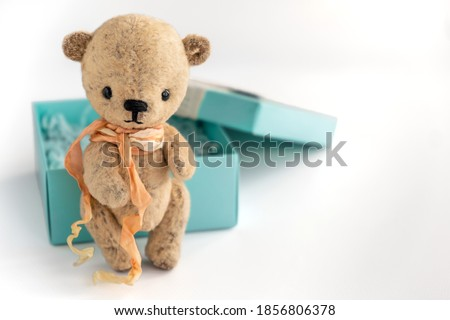 A vintage handmade teddy bear stands next to a gift box on a white background. Gift for an important holiday. Selective focus. Close-up. Copy space. Royalty-Free Stock Photo #1856806378