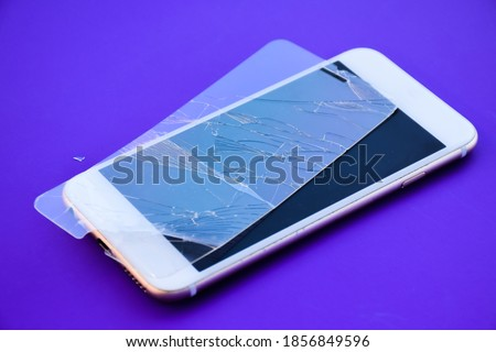 A broken glass mobile phone screen protector is placed on the mobile phone screen.