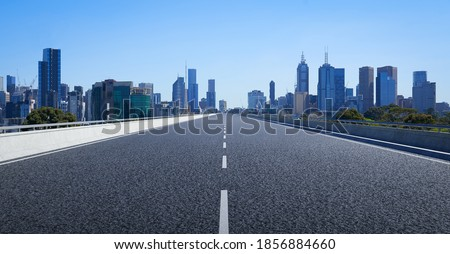 Perspective straight empty highway road with modern cityscape. Morning scene view .